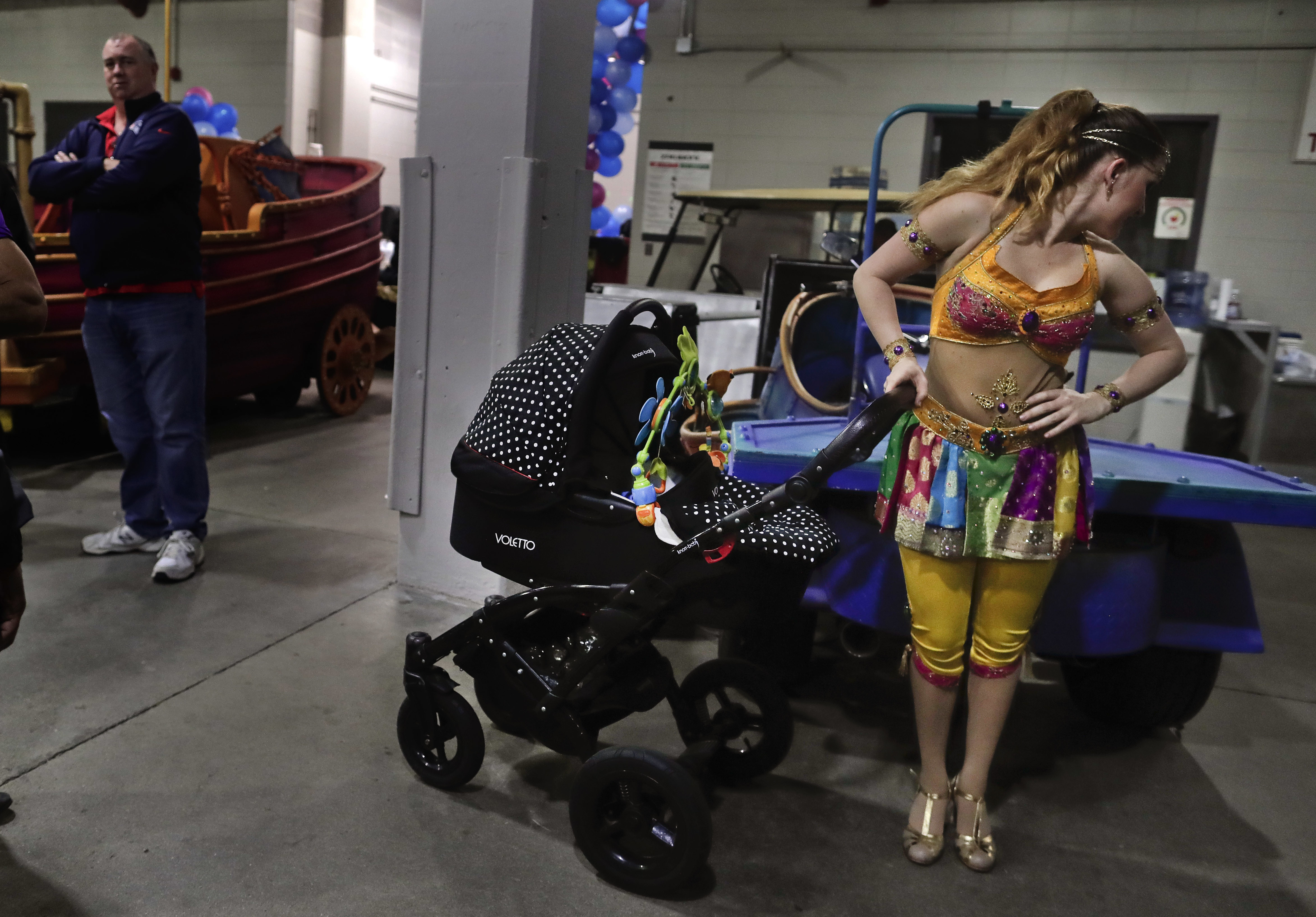Ringling Bros. high wire performer Anna Lebedeva stands next to her 3-month-old son, Amir, in his stroller while waiting to go on for the show's finale on May 5, 2017, in Providence, R.I. (Julie Jacobson/Associated Press)
