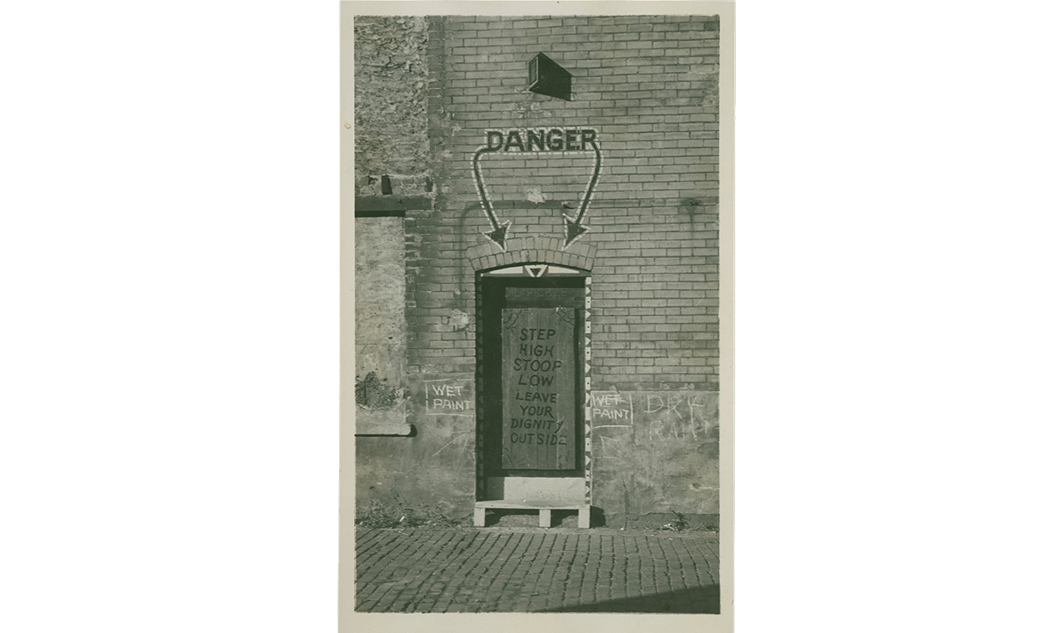 The Dill Pickle became known for its entryway, which added to its mystique. The alley's orange door was marked by a green light and inscribed with the phrase 'Step High, Stoop Low, Leave Your Dignity Outside.' (Courtesy Newberry Library)