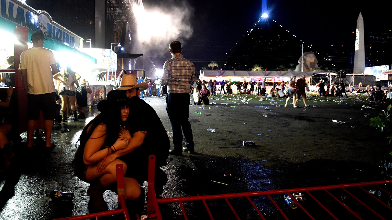 People take cover at the Route 91 Harvest festival after a gunman opened fire on the festival from a room in the Mandalay Bay Resort and Casino in Las Vegas. (David Becker/Getty Images)