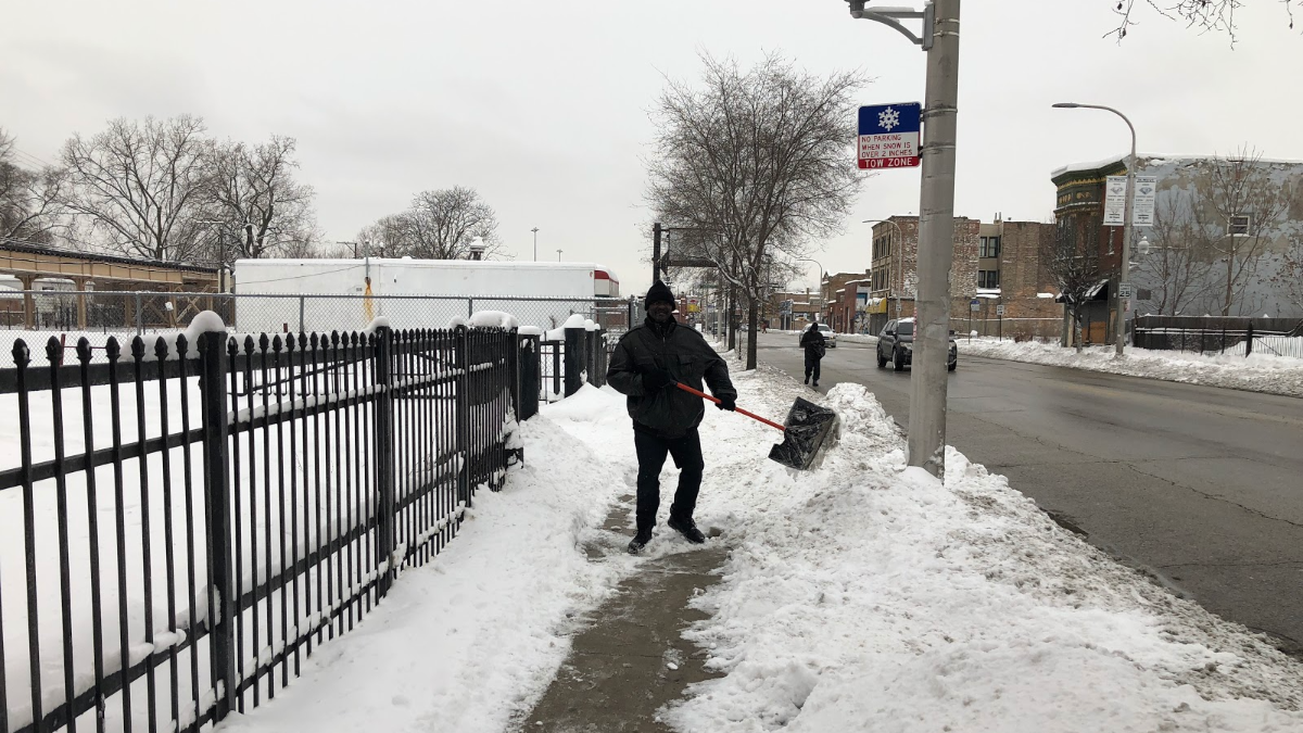 Grayson shovels on Sunday afternoon. 'The snow's been coming down pretty tough,' he said. 'All we can do is just keep shoveling.' (Greta Johnsen/WBEZ)