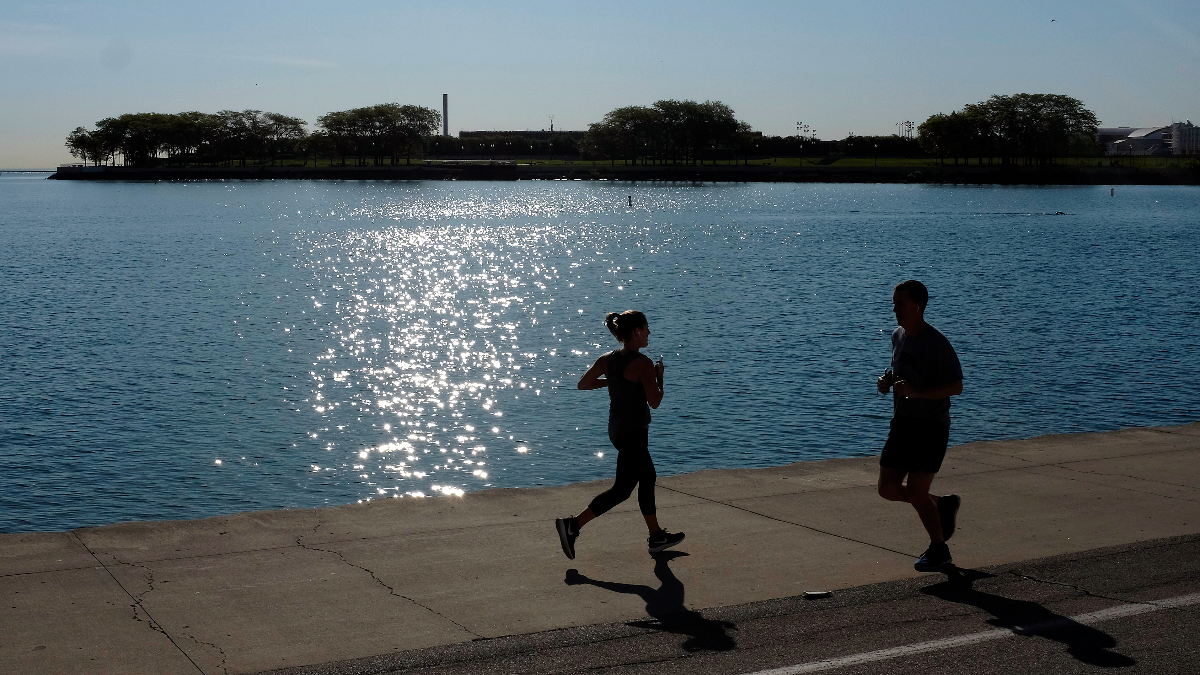 Runners jog along the shore of Lake Michigan in Chicago in June 2017. Mayor Rahm Emanuel said President Donald Trump's decision to pull out of the Paris climate accord is a poor attempt to pit environmental protection and economic growth against each other. (AP Photo/Kiichiro Sato)