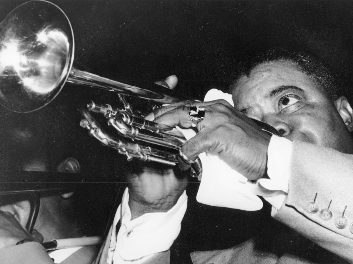 Legendary jazz musician Louis Armstrong plays his trumpet during an Oct. 1952 performance with his band. (AP Photo)