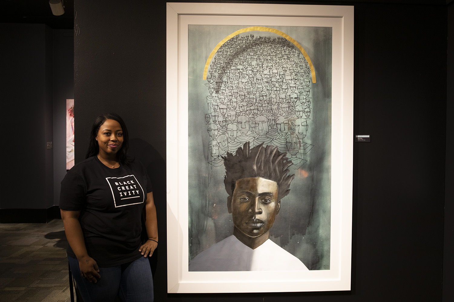 "Arts and creative manager Tiffany Malone stands next to Brian ""Golden's Promises…promises."" (Arionne Nettles/WBEZ)"