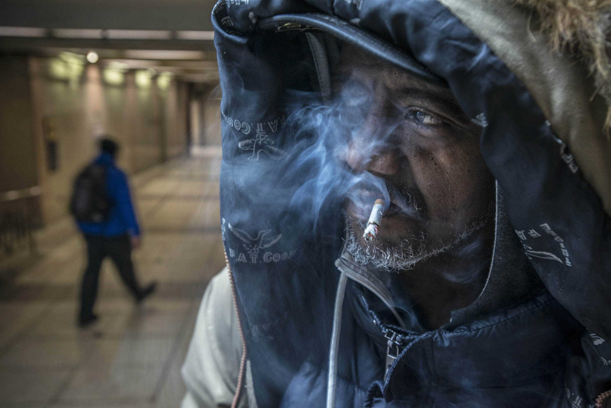 Just outside of the Metra Train station, Reggie smokes one of the many discarded cigarettes he picked up along the streets and sidewalks of downtown Chicago. (Photo courtesy of Lloyd Degrane)