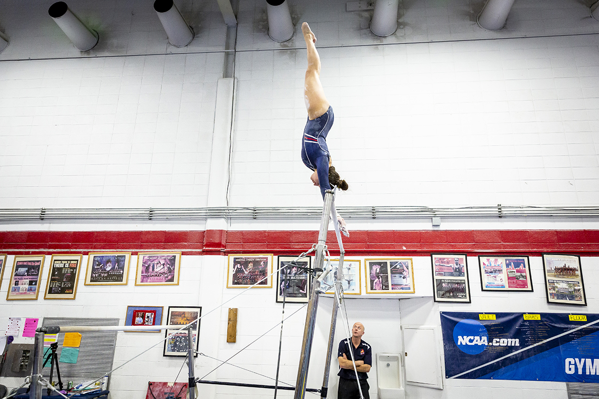 Coach Peter Jansson watches as senior Jenna Squillo completes her bar routine this winter.