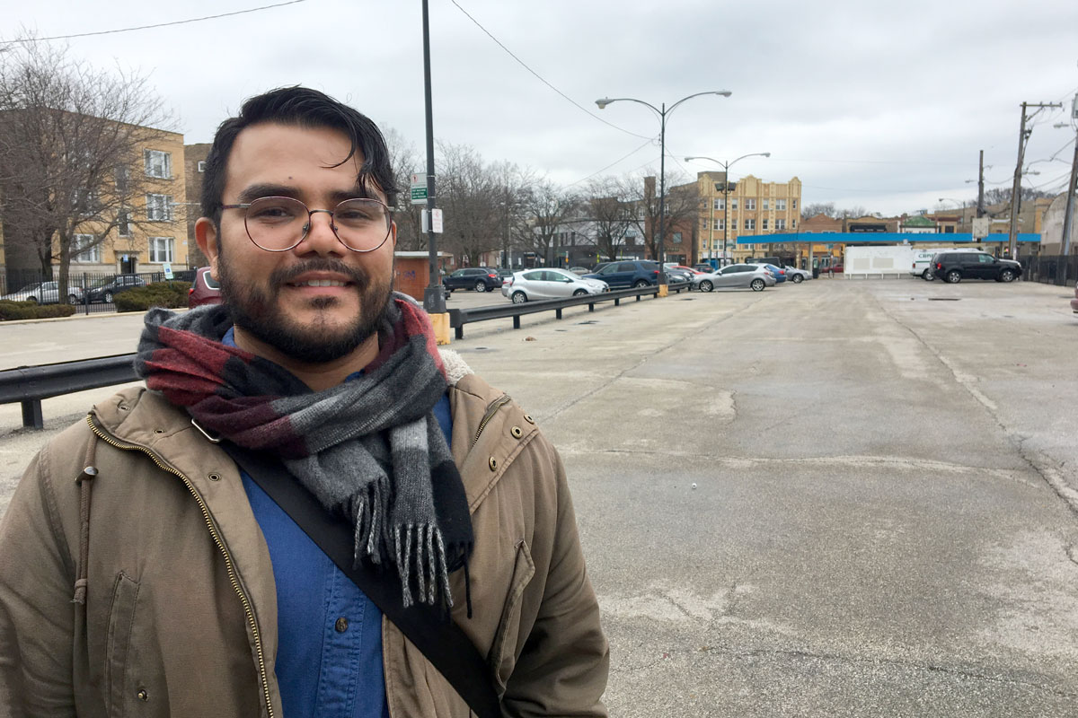 Christian Diaz of the Logan Square Neighborhood Association stands in the Emmet Street parking lot, a city-owned lot where housing advocates envision an affordable TOD development for working-class Latino families that might otherwise be priced out of the rapidly gentrifying neighborhood (Odette Yousef/WBEZ)