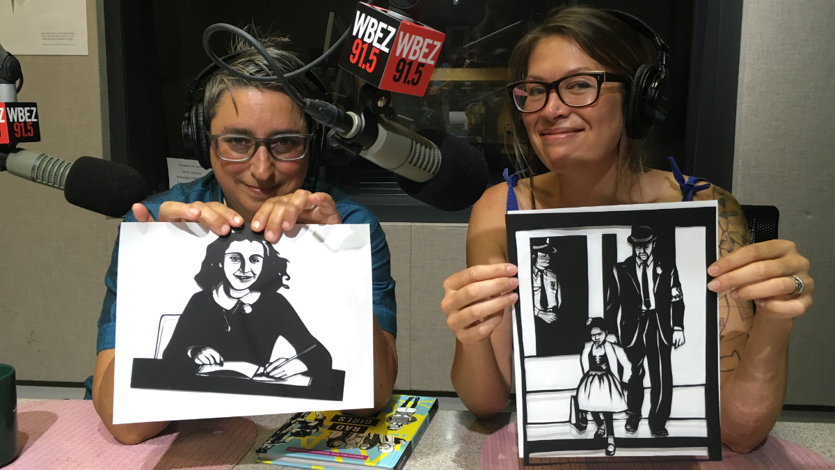 Author Kate Schatz (right) holds a hand-cut paper illustration of civil rights activist Ruby Bridges created by illustrator Miriam Klein Stahl (left), who is seen holding an illustration of famed diarist Anne Frank. (Justin Bull/WBEZ)