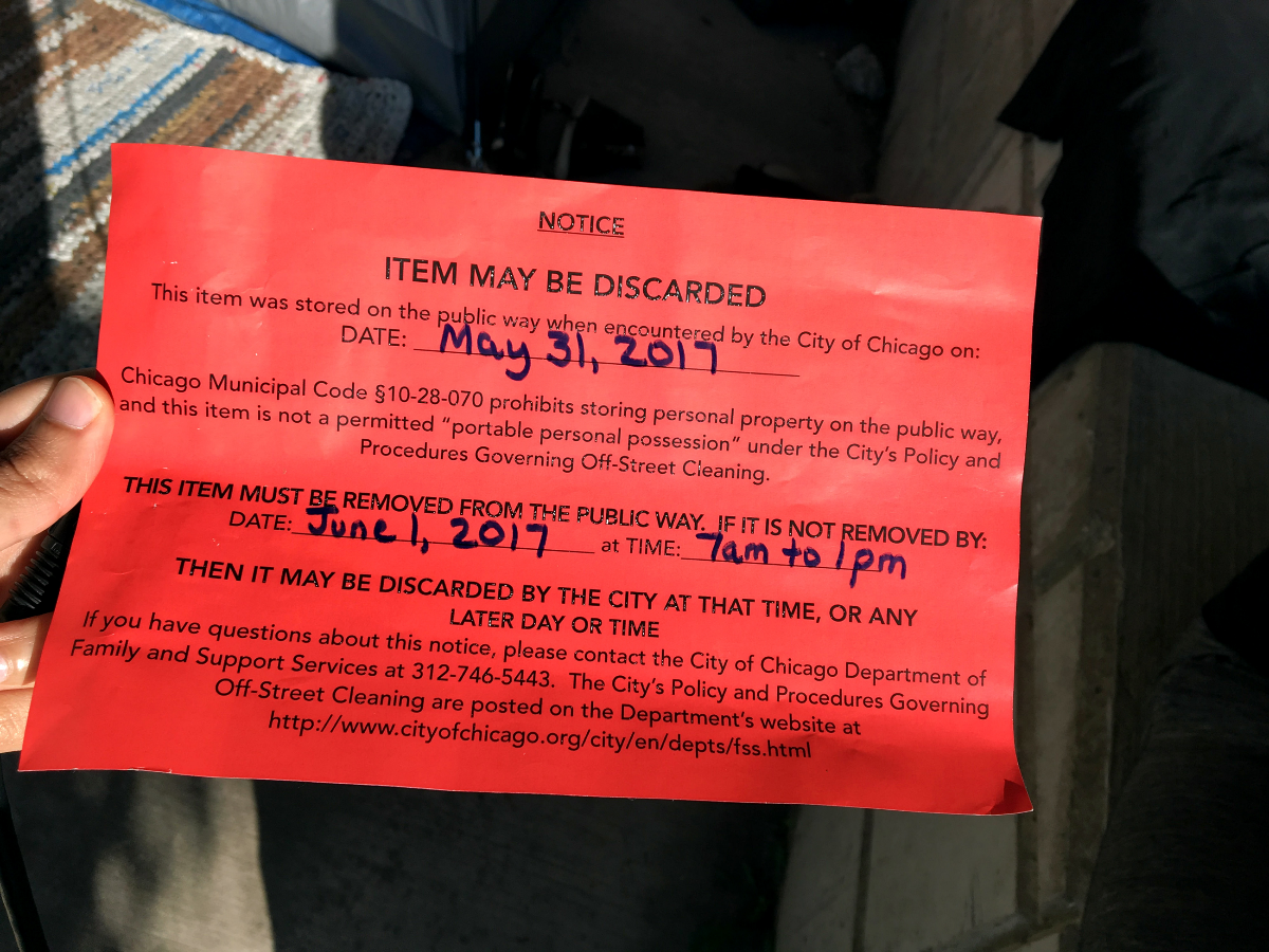 Shawn Smith and Amie Moore said Chicago police officers regularly visit them to post these notices of intention to remove the couple's tent. The notices cite municipal ordinance and a non-binding agreement on sidewalk cleaning policies as reasons for confiscating the couple's property. (Odette Yousef/WBEZ)