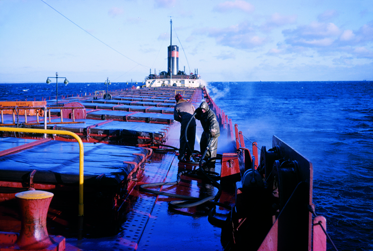 Two crew members hose ice off the deck on a vessel in late November, 1962. (Courtesy Deckhand: Life on Freighters of the Great Lakes, by Nelson Haydamacker, published by University of Michigan Press, c. 2009)