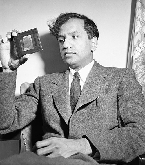 Dr. Subrahmanyan Chandrasekhar, an India-born professor of theoretical astrophysics at University of Chicago's Yerkes observatory, holds a lantern slide which he uses to explain a new theory of improved weather forecasting through a better understanding of movements in the Earth's atmosphere and the gases within the sun and other stars. (AP Photo/Ernest K. Bennett)