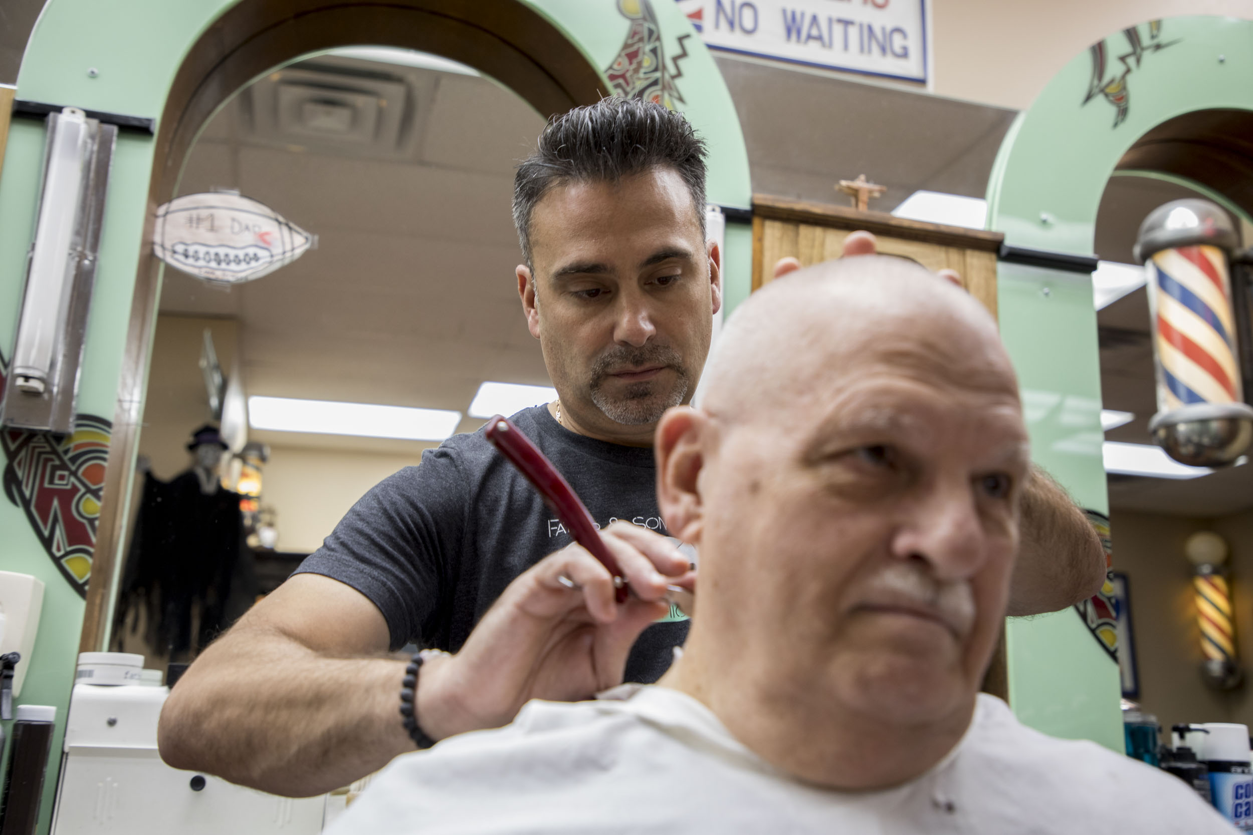 Father and Son co-owner Pete Faraci uses a straight razor to finish a haircut. (Andrew Gill/WBEZ)