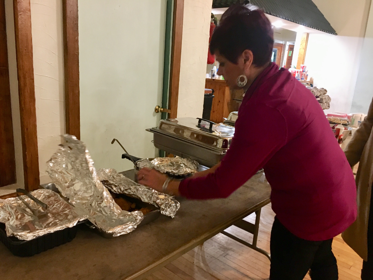 East Chicago resident Debbie Bolanos sets out food at the shelter. (Michael Puente/WBEZ)