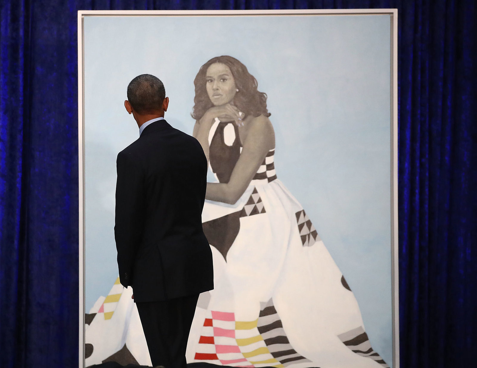 Barack Obama gazes at his wife's newly unveiled portrait on Monday. The painting of Michelle Obama will be on display through November in the National Portrait Gallery's 'Recent Acquisitions' section. (Mark Wilson/Getty Images)