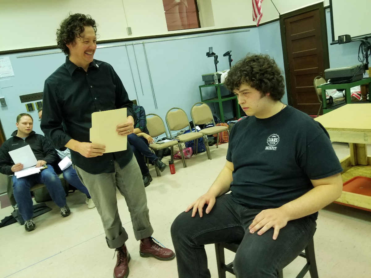 Lead Senn High School theater teacher Joel Ewing (left), who plays various male adults in the play, including a guidance counselor, 'juvenile diversion counselor,' and a victim's father. Brian Baren (right), 20, a graduate of Senn High School, plays the Dylan Klebold character. 'It's hard to act these scenes out,' he said. (Linda Lutton/WBEZ)