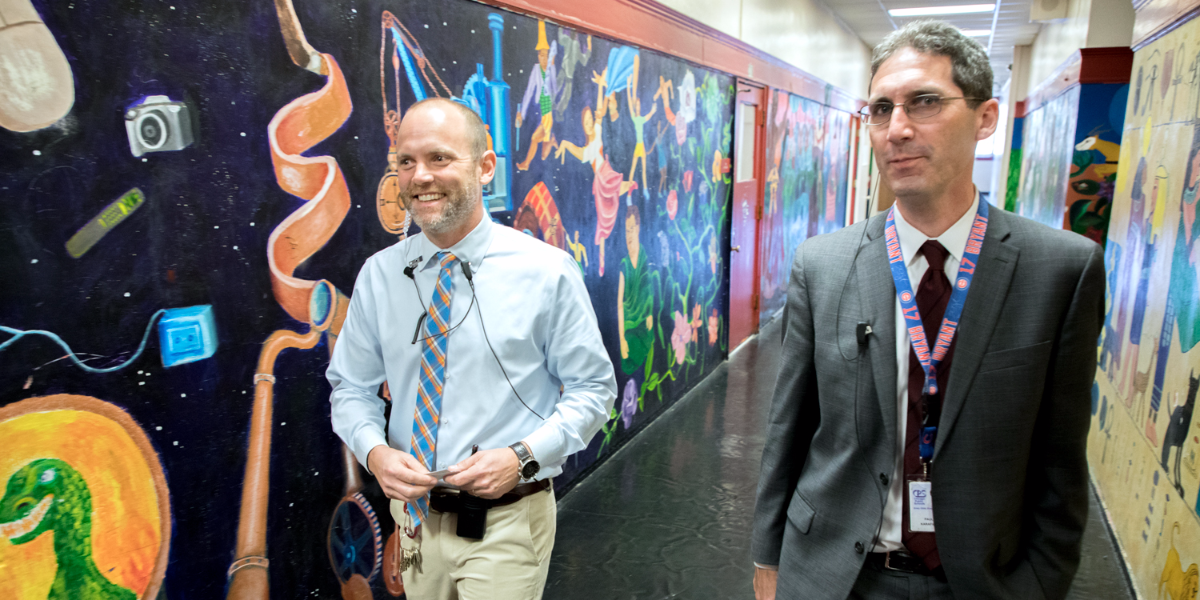 Lake View Assistant Principal Toney Vast-Binder (left) and Principal Paul Karafiol (right) walk the halls of the North Side neighborhood high school. (Andrew Gill/WBEZ)