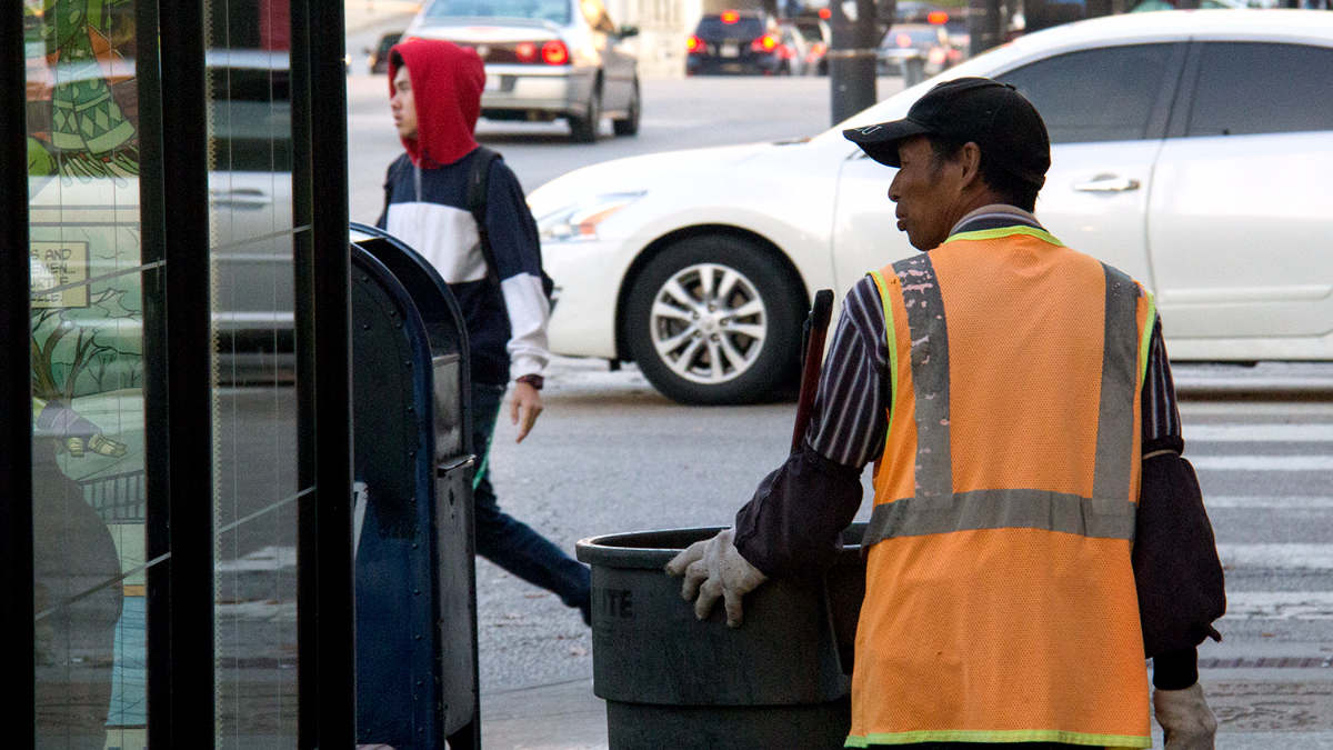 A man pushes a trashcan on wheels in Chinatown in November 2016. (WBEZ/Andrew Gill)
