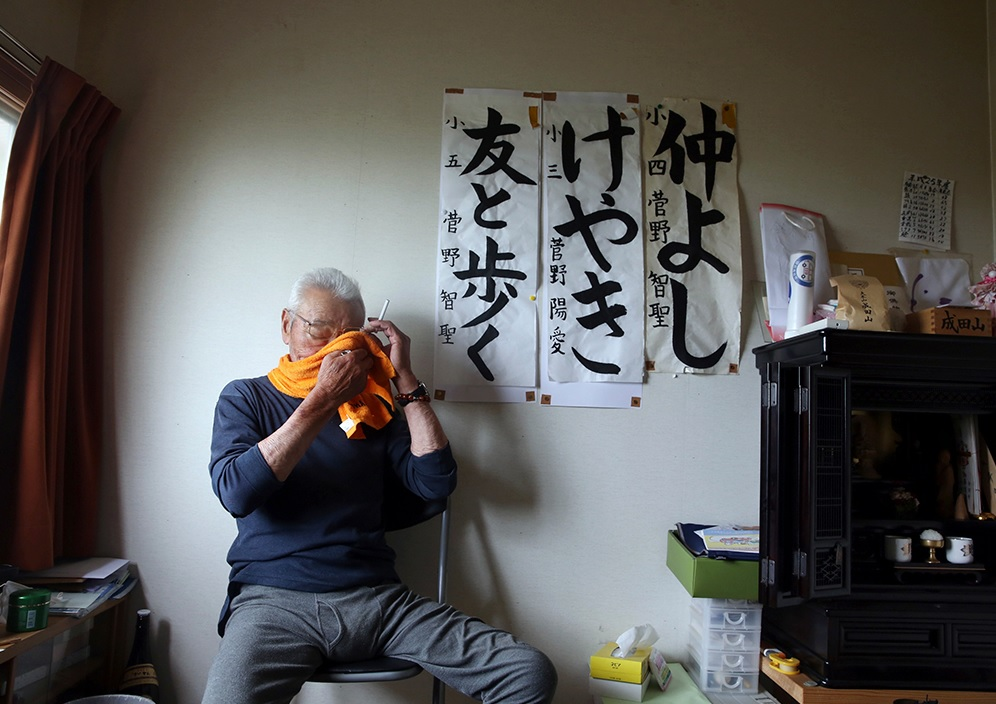 Noboru Suzuki, 81, at his temporary housing in Rikuzentakata city, Iwate, on July 26, 2013. Behind him is an annual calligraphy gift from his grandchildren marking the years he has been living in this space.(Noboru Suzuki/Nikkei Photo/Courtesy of Kizuna Archive 2014).