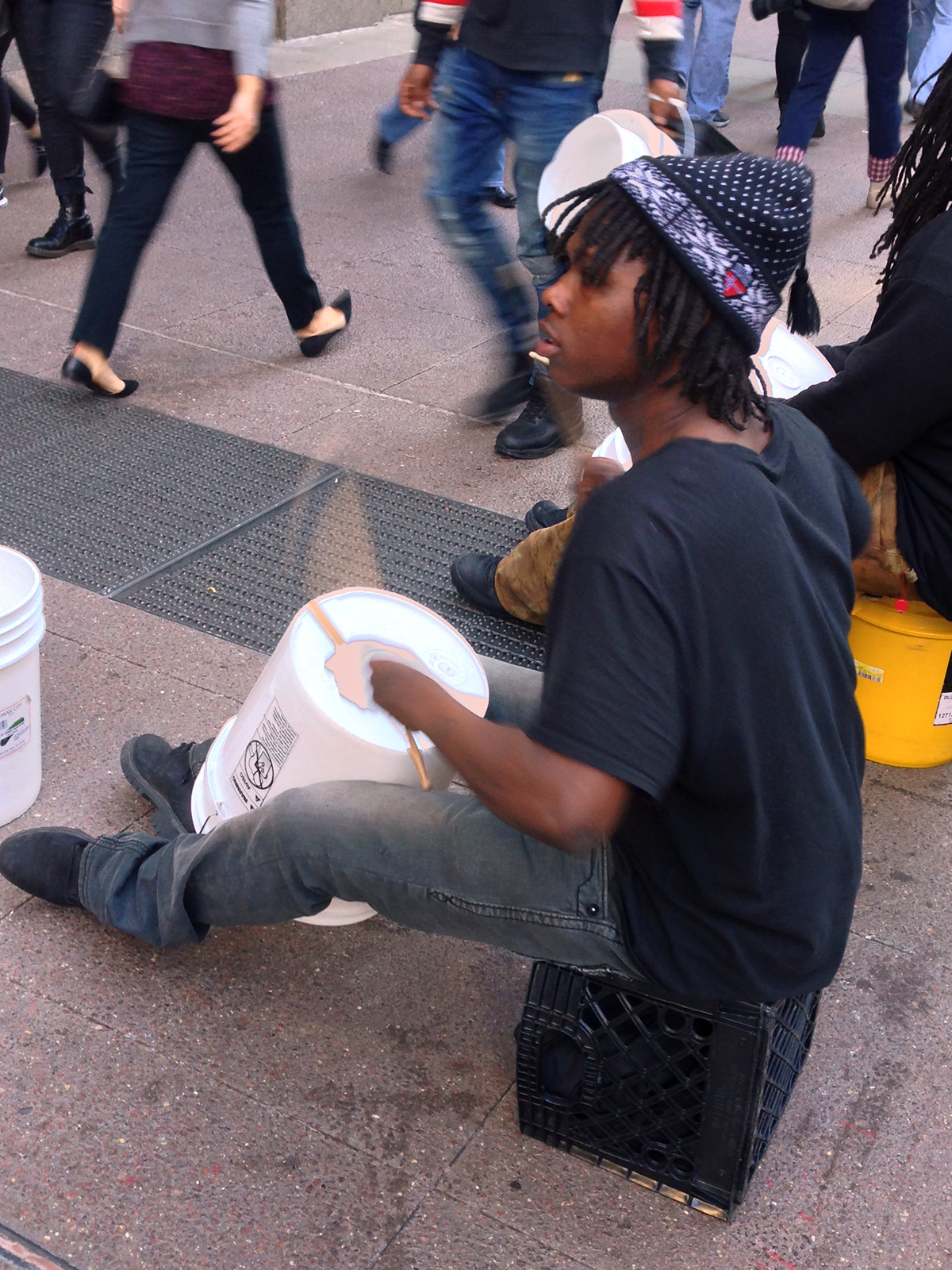 A so-called bucket boy performs downtown, where a debate is taking place over whether street performers are a nuisance or add to the city's charm. (Claire Donnelly/WBEZ)