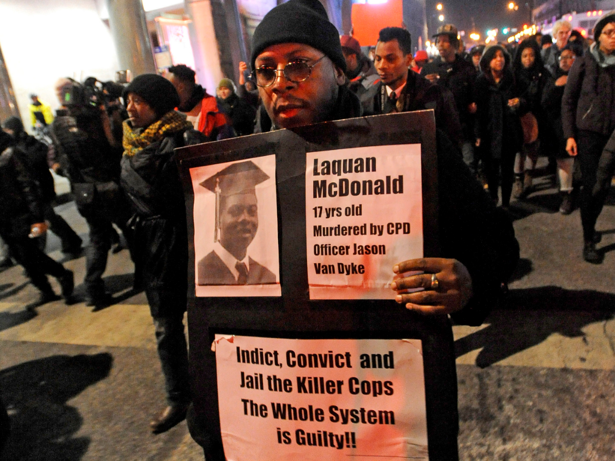 A man holds a sign with a photo of Laquan McDonald on it, during a protest of the police shooting 17-year-old McDonald, in Chicago on Nov. 24, 2015. (AP Photo/Paul Beaty)