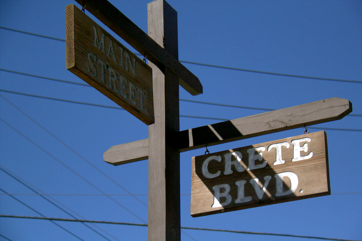 Many street signs in Crete are carved into rustic cross beams, part of its small town appeal to some residents. (Chris Hagan/WBEZ)