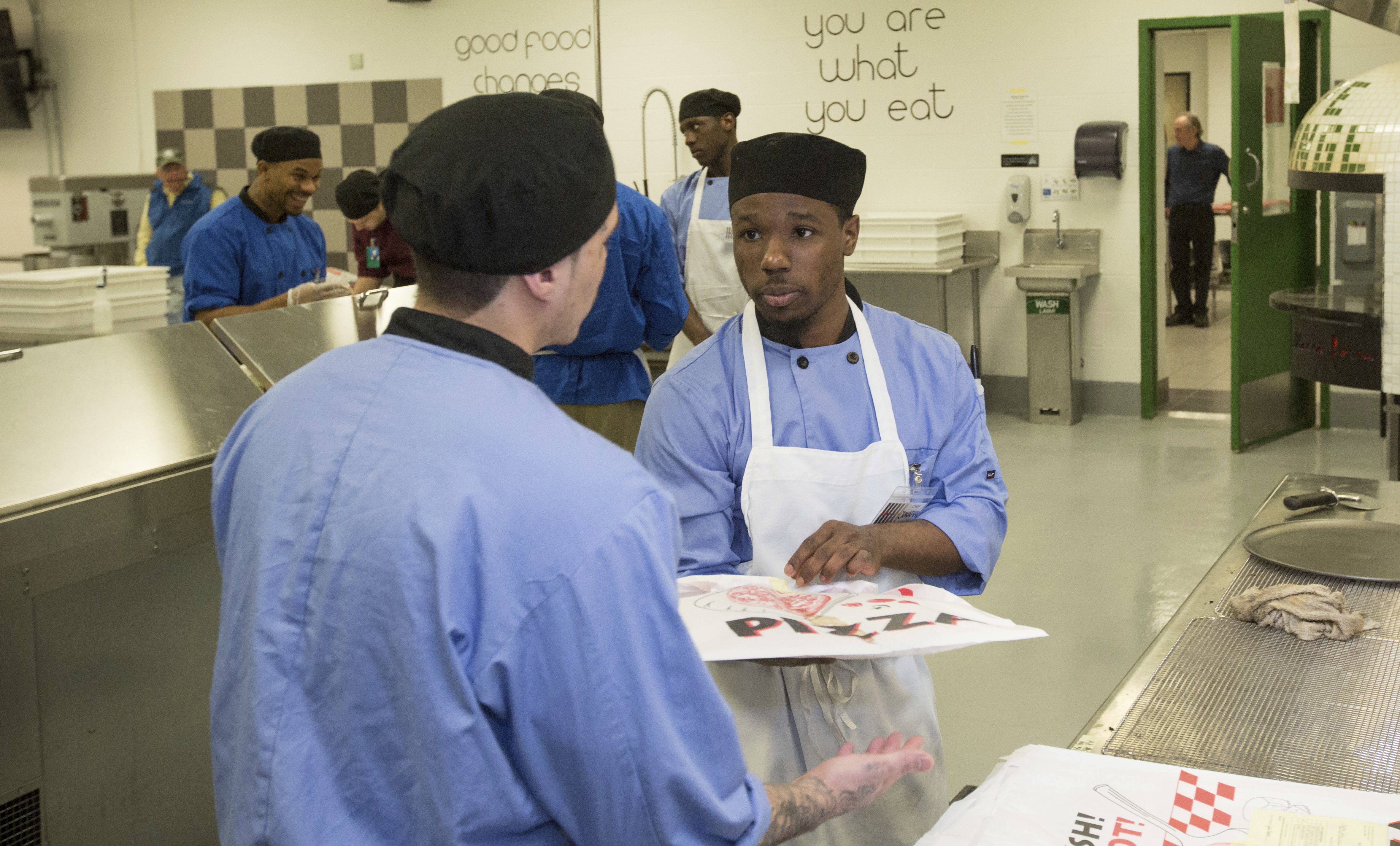Inmate Jonathan Scott, right, works in the kitchen at the Cook County Jail in Chicago. Scott is participating in the jail's 'Recipe for Change' program while he waits for trial after his 2015 arrest on an armed robbery charge. (AP Photo/Teresa Crawford)