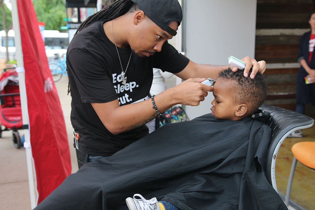Tribe Sankofa Waters, who's almost 2 years old, gets his hair cut by Ivan Hairston of Hyde Park Barber Studio. (Arionne Nettles/WBEZ)