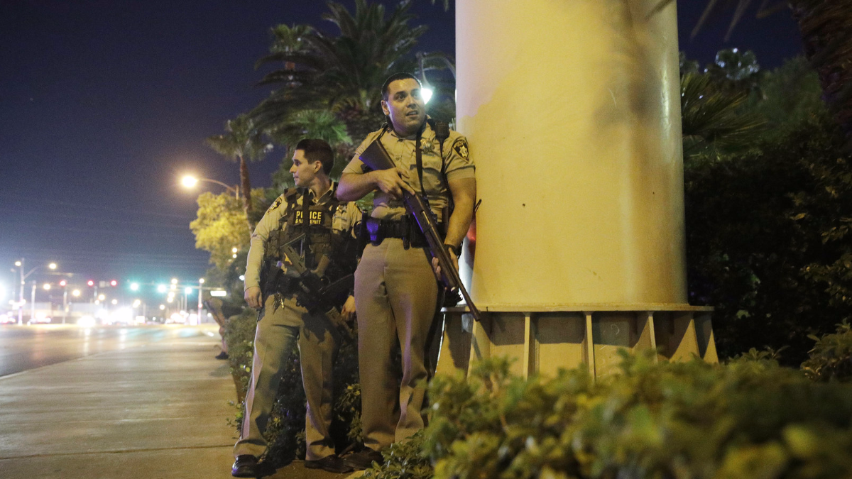 Police officers take cover near the scene of a shooting near the Mandalay Bay Resort and Casino on the Las Vegas Strip on Sunday. (John Locher/AP)